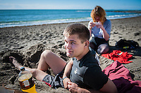 Aberystwyth, West Wales, UK Weather: A young man enjoys the sunshine on the beach in Aberystwyth, Wales.