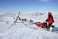 Tuesday March 13, 2007   ----   Paul Gebhart runs past tripod markers in the Topkok hills on his way to Nome