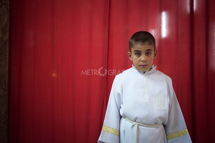 16/11/14. Alqosh, Iraq. 10 year old Iraqi-Christian orphan Milad is pictured in the Virgin Mary Monastery's Der Saida Church where he serves as an alter boy during Sunday services.