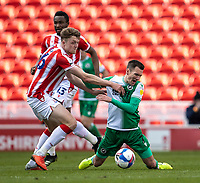 5th April 2021; Bet365 Stadium, Stoke, Staffordshire, England; English Football League Championship Football, Stoke City versus Millwall; Jed Wallace of Millwall is tackled by Harry Souttar of Stoke City