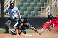 Austin Bossart (17) of the Lakewood BlueClaws touches home plate with his hand ahead of the tag attempt by Kannapolis Intimidators catcher Daniel Gonzalez (8) as home plate umpire David Martinez at Kannapolis Intimidators Stadium on May 8, 2016 in Kannapolis, North Carolina.  The Intimidators defeated the BlueClaws 3-2.  (Brian Westerholt/Four Seam Images)
