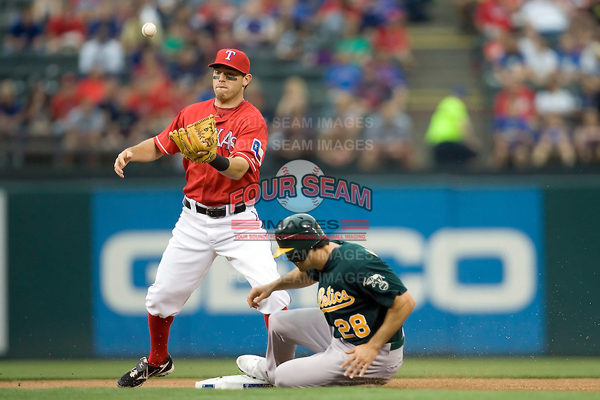 Texas Rangers second baseman Ian Kinsler (5) bobbles a throw while Oakland Athletics outfielder Conor Jackson (28) slides safely into second against the Oakland Athetics in American League baseball on May 11, 2011 at the Rangers Ballpark in  Arlington, Texas. (Photo by Andrew Woolley / Four Seam Images)