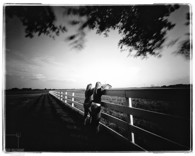 Girls looking over a wooden fence