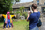 Scarecrow Festival at Kettlewell in Yorkshire 2013<br /> <br /> Posing for pictures as you get a chance to be a scarecrow yourself<br /> <br /> Scarecrows are made by local community and places in and around their front gardens.  Competition is fierce but it's all to raise money  for the local church  and other local projects to benefit the whole community.<br /> <br /> <br /> <br /> Picture by Gavin Rodgers/ Pixel 8000 <br /> <br /> 07917221968