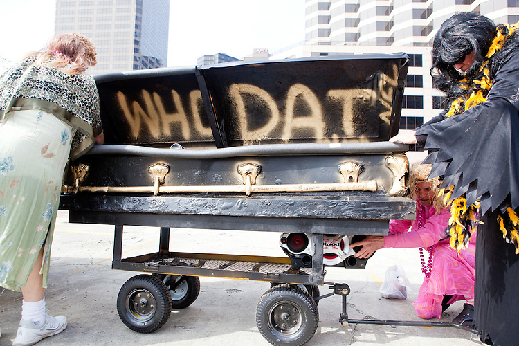 "(From L) Rodney Crout, Rodney Parent, and Michael Landeche prepare a funeral casket outfitted for the parade in Buddy D's honor on January 31, 2010 in New Orleans.<br /> <br /> Thousands of Saints fans wearing dresses paraded from the Louisiana Superdome to the French Quarter to honor a promise made by the late sportscaster and Saints super-fan Buddy Diliberto aka ""Buddy D"".<br /> <br /> In 1993 Buddy D, who passed away in 2005, remarked on air that if the Saints were to make it to the Super Bowl, he would wear a dress and dance down the streets.  The comment was repeated at various times and never forgotten by his listeners.<br /> <br /> Led by former New Orleans Saints quarterback Bobby Hebert, who has taken Buddy D's place on WWL radio, thousands made good on his promise for him, dancing, drinking, and cavorting their way down the street, alternately yelling out ""Who Dat!"" and ""Buddy D!"" in front of an onlooking crowd an estimated 85,000 people strong.<br /> <br /> The hard luck NFL team the New Orleans Saints has reached its first Super Bowl in team history, after 43 years largely filled with losing seasons and futility.  It is difficult to travel anywhere in the area without some reminder of this fact, as the team and city are intertwined perhaps like no other sports franchise in this country."