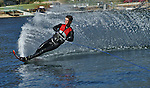 Water skier cuts through smooth glassy water creating a fine spray.