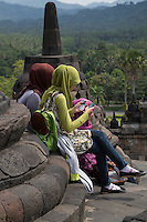 Borobudur, Java, Indonesia.  Young Indonesian Girl in Scarf and Levis Checking Cell Phones.