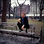 Man in suit sitting on top of park bench holding a banana