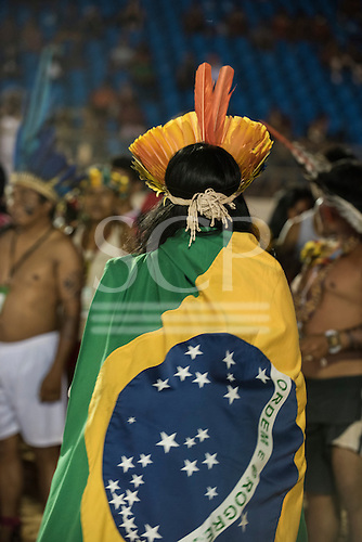 A protestor wears the Brazilian flag wrapped around him to demonstrate that he is as much a citizen of Brazil and non-indigenous people during a protest against PEC 215, a proposal to amend the Brazilian constitution to water down indigenous rights at the International Indigenous Games, in the city of Palmas, Tocantins State, Brazil. Photo © Sue Cunningham, pictures@scphotographic.com 28th October 2015