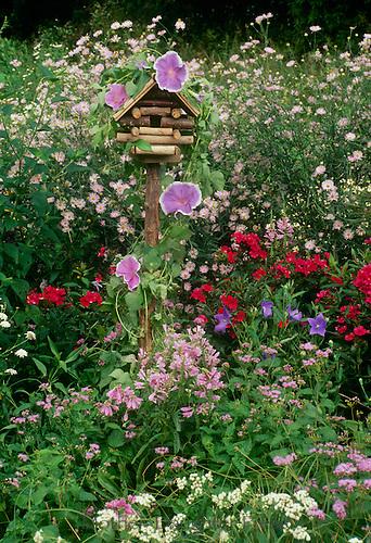 Garden birdhouse as art with blooming flowers in summer garden, Missouri USA