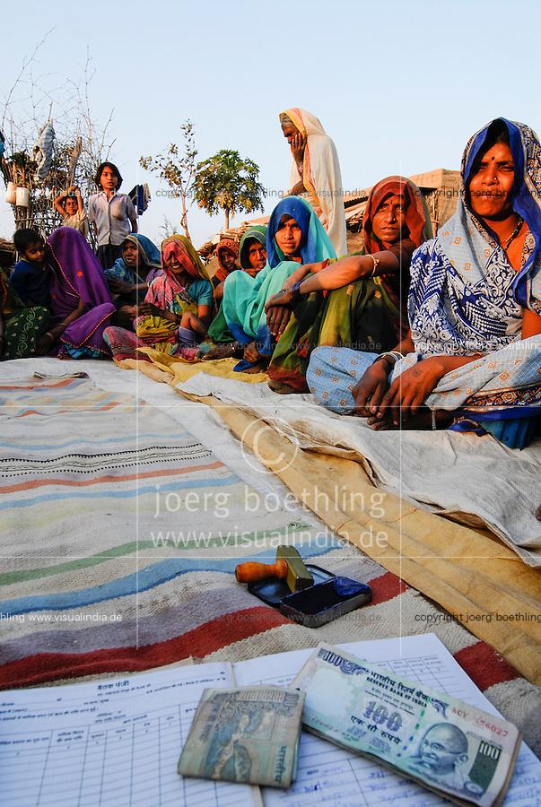 INDIA, Madhya Pradesh , rural women bank in village, illiterate women sign with thumb print, hundred rupee banknotes with Mahatma Gandhi image