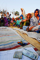 INDIA, Madhya Pradesh , rural women bank in village, illiterate women sign with thumb print, hundred rupee banknotes with Mahatma Gandhi image