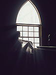 Sunlight lit silhouette of a beautiful young woman sitting on a window sill in a house Image © MaximImages, License at https://www.maximimages.com