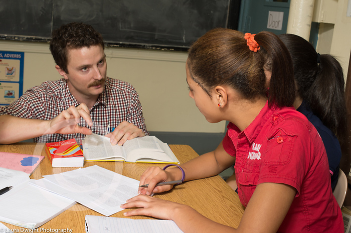 Education high school classroom scenes male teacher working with female student in class