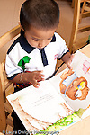 Education preschool 3-4 year olds boy looking at picture book vertical