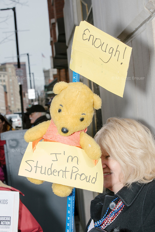 """People take part in the March For Our Lives protest, walking from Roxbury Crossing to Boston Common, in Boston, Massachusetts, USA, on Sat., March 24, 2018, in response to recent school gun violence. Here, a person holds a Winnie the Pooh stuffed animal and signs reading """"Enough!"""" and """"I'm student proud."""""""