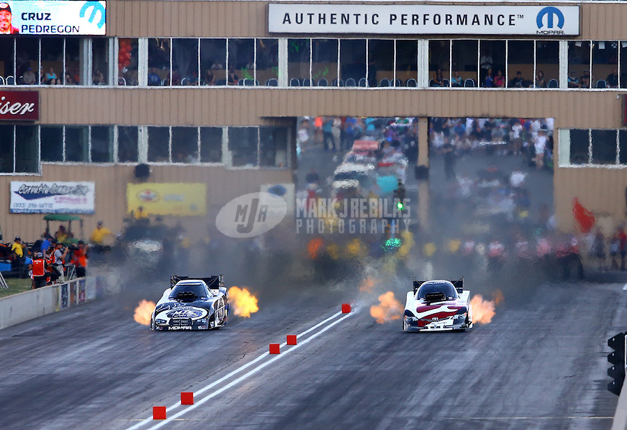 Jul. 20, 2013; Morrison, CO, USA: NHRA funny car driver Cruz Pedregon (right) races alongside Jack Beckman during qualifying for the Mile High Nationals at Bandimere Speedway. Mandatory Credit: Mark J. Rebilas-