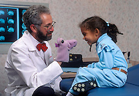 Pediatric doctor relaxes a young patient with a hand puppet.