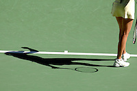 The shadow of a woman playing tennis on a court about to serve.