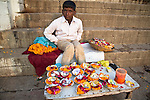 Indian boy selling flower offerings on the ghats of the Ganges River in Varanasi, Uttar Pradesh, India