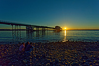 Pictured: Three young people sit on the beach to watch the sunrise as seen through the RNLI boat station in Mumbles, near Swansea, Wales, UK. Sunday 13 June 2021<br /> Re: High temperatures and sunshine has been forecast for most of the UK.