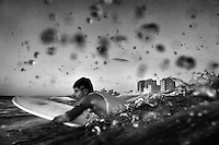 20 year old surfer Omar Rhim paddles out into the Mediterranean Sea from Gaza City.