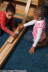 Preschool classroom 3-4 year olds two girls playing together with toy trains and ramp and  road they made out of blocks