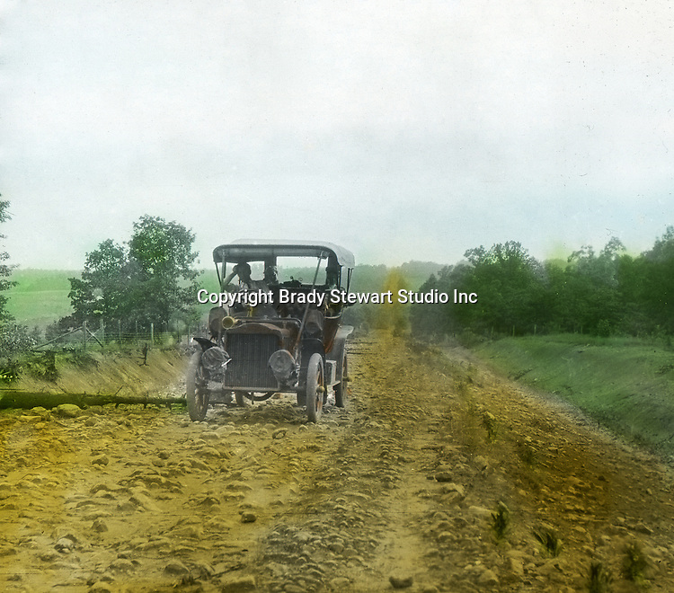 Greensburg PA:  The 1906 Buick Model F broken down after running over a tree on a rocky road outside Greensburg PA.  To give family and friends a better feel for the adventure, he hand-color black and white negatives into full-color 3x4 lantern slides.  The Process:  He contacted a negative with another negative to create a positive slide.  He then selected a fine brush and colors and meticulously created full color slides.