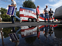 Yard signs were passed out and stories exchanged as Trump supporters gathered around an official Donald Trump for President bus parked outside Kohr Brothers Frozen Custard Tuesday afternoon in Charlottesville, Va. Photo/The Daily Progress/Andrew Shurtleff