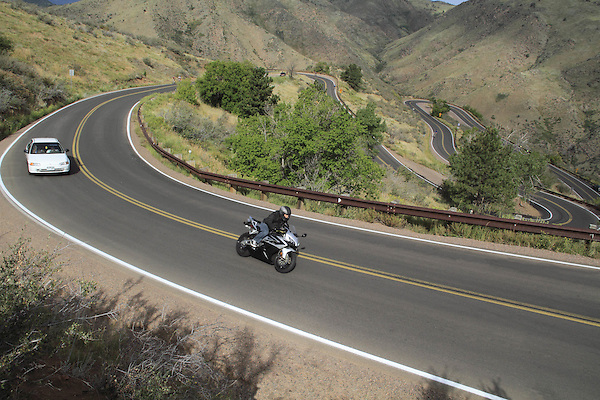 Motorcycle and car ascending Lookout Mountain, Golden, Colorado, USA. .  John offers private photo tours in Denver, Boulder and throughout Colorado. Year-round.