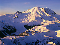 Early morning light displays the Sunrise side of Mount Rainier. Sunrise Lodge, Visitor Center buildings and snowed-in parking area are visible at bottom left, with Sourdough Ridge in the foreground. Little Tahoma is the rocky pinnacle exposed at the left of Mount Rainier's summit.....Photographed on Provia 100 film in 6X7 format.