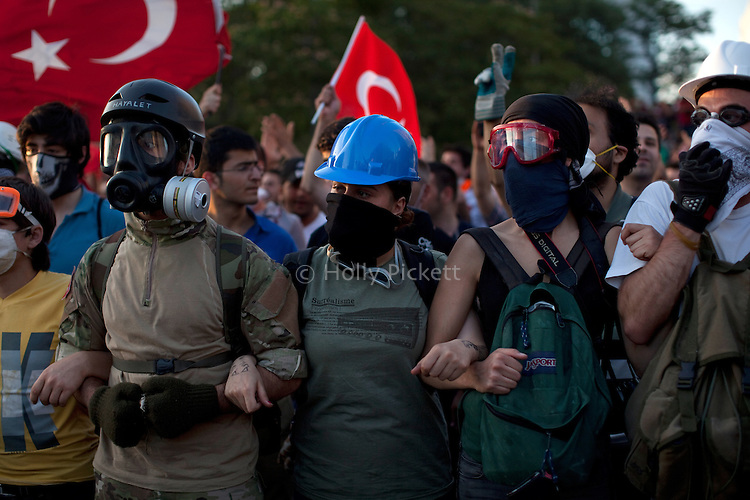 Protesters link arms to keep their fellow protesters removed from police, during an evening lull in violence with police in Taksim Square, Istanbul, Turkey, June 11, 2013. One of the first actions upon their arrival in the square was to take down all of the banners hung by protesters along the building's outside wall. What started as a peaceful sit-in to save a small park near Taksim Square from being turned into a shopping mall has turned into large-scale anti-government demonstrations in cities across Turkey. In Istanbul, the protests have united communists, nationalists, anarchists, social liberals, and others unhappy with Prime Minister Recep Tayyip Erdogan's policies. Taking inspiration from the Occupy Wall Street movement in the United States, thousands of protesters have set up tents and are occupying the park in hopes of making their voices heard.