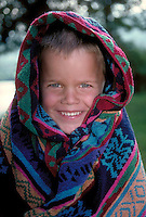 Smiling young boy with a colorful towel wrapped around his head.