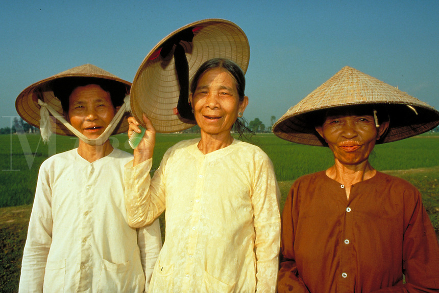 Farm commune workers in rice field outside Hanoi take time out to pose for picture. 3 old women. Hanoi, Vietnam.