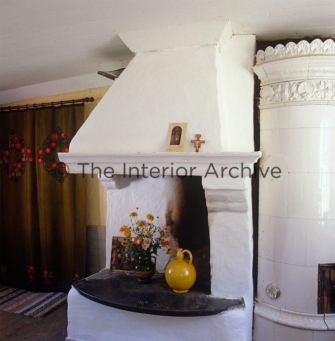 A corner fireplace and tiled stove stand side by side in this living room