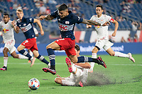 FOXBOROUGH, MA - MAY 22: Gustavo Bou #7 of New England Revolution leaps over a tackle by Brandon Bye #15 of New England Revolution during a game between New York Red Bulls and New England Revolution at Gillette Stadium on May 22, 2021 in Foxborough, Massachusetts.