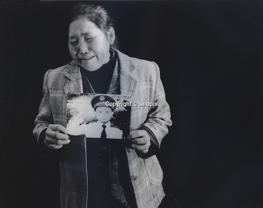 """Mrs Xiang, 40, holds a picture of her son Ren Pan, who was 4 and half years old when he was stolen 9th September 2003. The message reads; """"Hope my son can come back home safe.""""<br /> Jun 2007<br /> <br /> photo by Richard Jones / Sinopix"""
