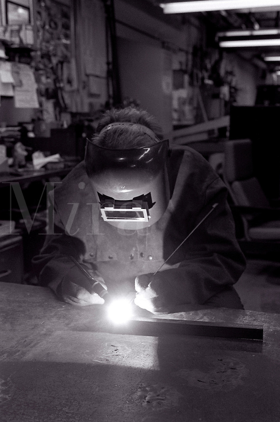 Welder at work in a machine shop.