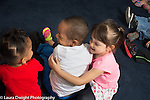 Education preschool 4 year olds group of friends two girls and a boy laughing and hugging before circle time starts