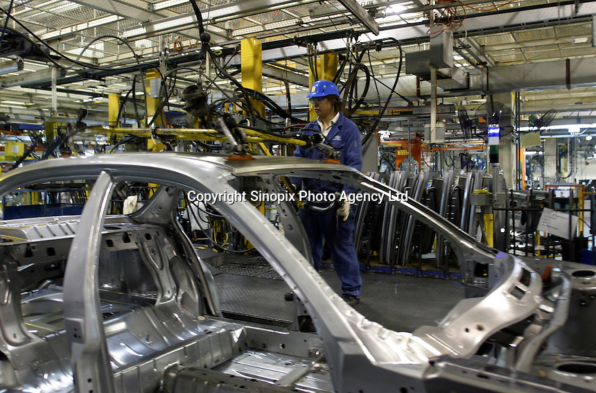 A Chinese worker operates on the assembly line at the Shanghai General Motors (SGM) plant in Shanghai, China. SGM is a joint-venture between General Motors and the Shanghai Automotive Industries Corporation..