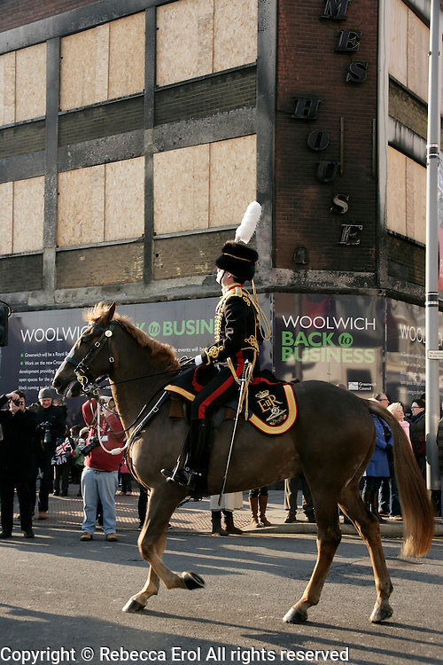 A member of the King's Troop Royal Horse Artillery march past a building burnt out during the London riots in Woolwich on their way to their new home nearby 2012