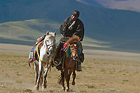 Tibetan Nomads on Horseback near lake Namtso which is the highest saltwater lake in the world at an elevation of 4870 meters.