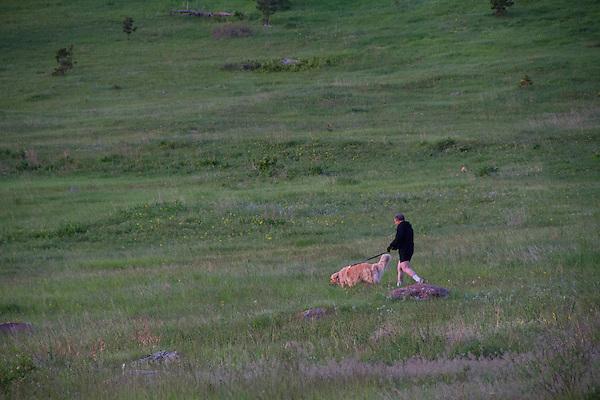 Man walking dog in Foothills in summer, Boulder, Colorado