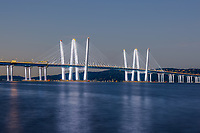 The Governor Mario M. Cuomo Bridge, illuminated with white lights, spans the Hudson River during morning twilight.
