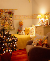 A small bedecked Christmas tree illuminates this child's bedroom