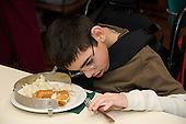 MR / Albany, NY.Langan School at Center for Disability Services .Ungraded private school which serves individuals with multiple disabilities.Child prepares to eat his lunch as he works hard to grasp fork. A plate guard will help keep food on his plate and a Dycem keeps the plate from sliding on the table as he eats. Boy: 11, cerebral palsy, expressive and receptive language delays.MR: Bro12.© Ellen B. Senisi