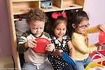 Education Preschool 2-3 year olds group of two girls and boy pretend play driving using plates as steering wheels