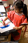 Education preschoool children ages 3-5 art activity girl in smock painting with poster paint vertical