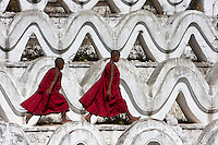 Myanmar, Burma.  Mingun, near Mandalay.  Two Young Novice Bhuddist Monks Walking on the Hsinbyume Paya, a Stupa Built in 1816.