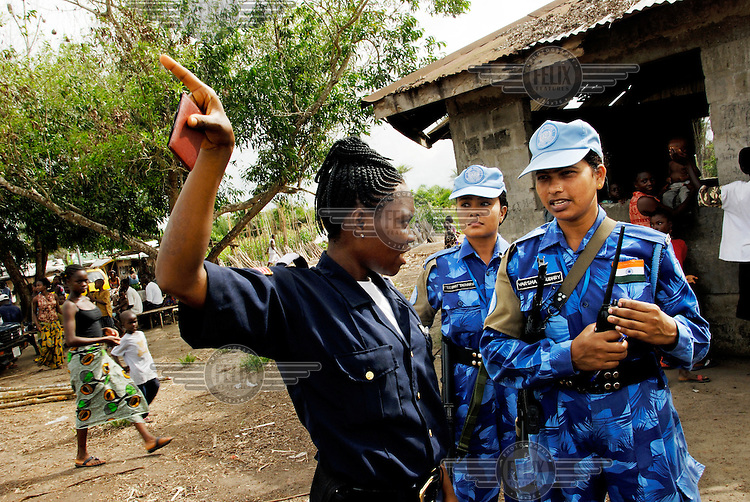 """LIBERIA, Monrovia, 05/04/2007..Winnefred, a Liberian National Police officer, and Varsha discuss potential problems in the area whilst on Joint Task Force patrol in the Duport Rd area of Monrovia. """"On the Job"""" training forms a vital aspect of the unit's role in helping to build capacity in the Liberian National Police Force...© 2007 Aubrey Wade. All rights reserved."""